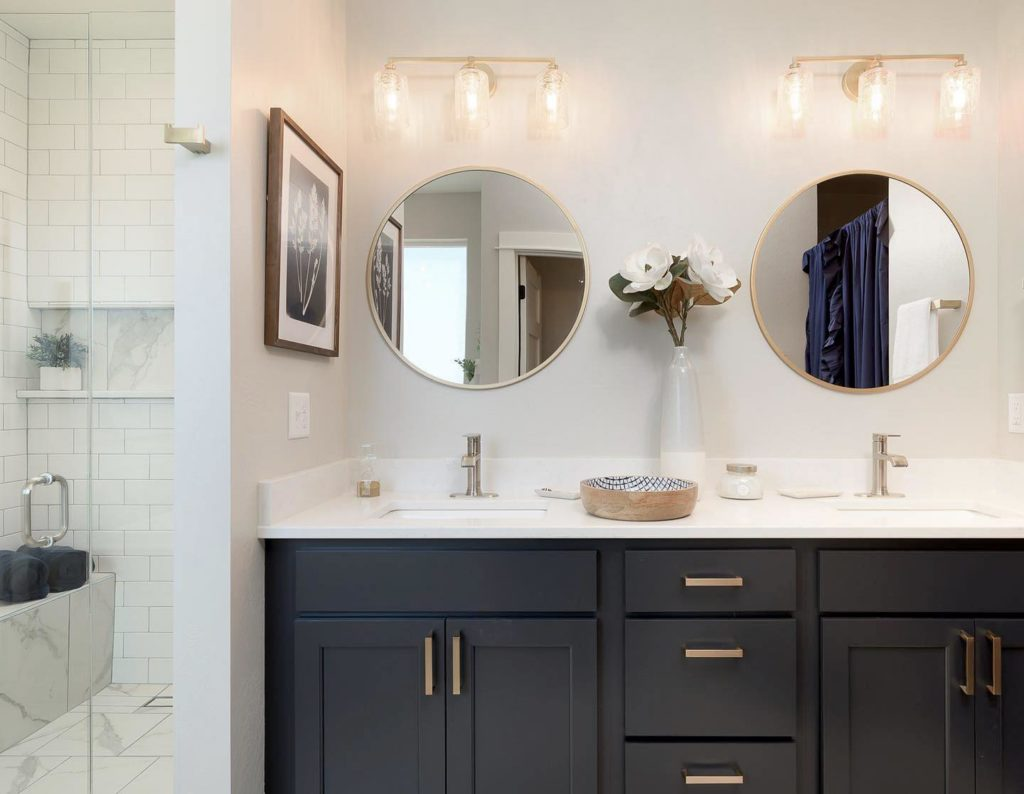modern bathroom with gold accents double sinks with round mirrors and white interior walls - ami sayer bozeman real estate